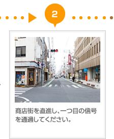 商店街を直進し、一つ目の信号を通過してください。